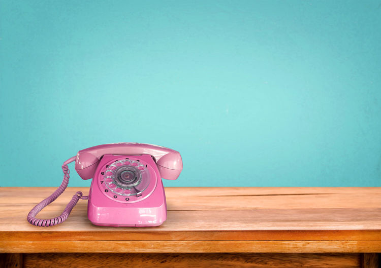Old retro pink telephone on table with vintage green pastel background Desk Office Old-fashioned Vintage Style Antique Communication Connection Indoors  Landline Phone No People Object Old-fashioned Phone Pink Color Retro Styled Rotary Phone Table Technology Telephone Telephone Line Telephone Receiver Wood - Material