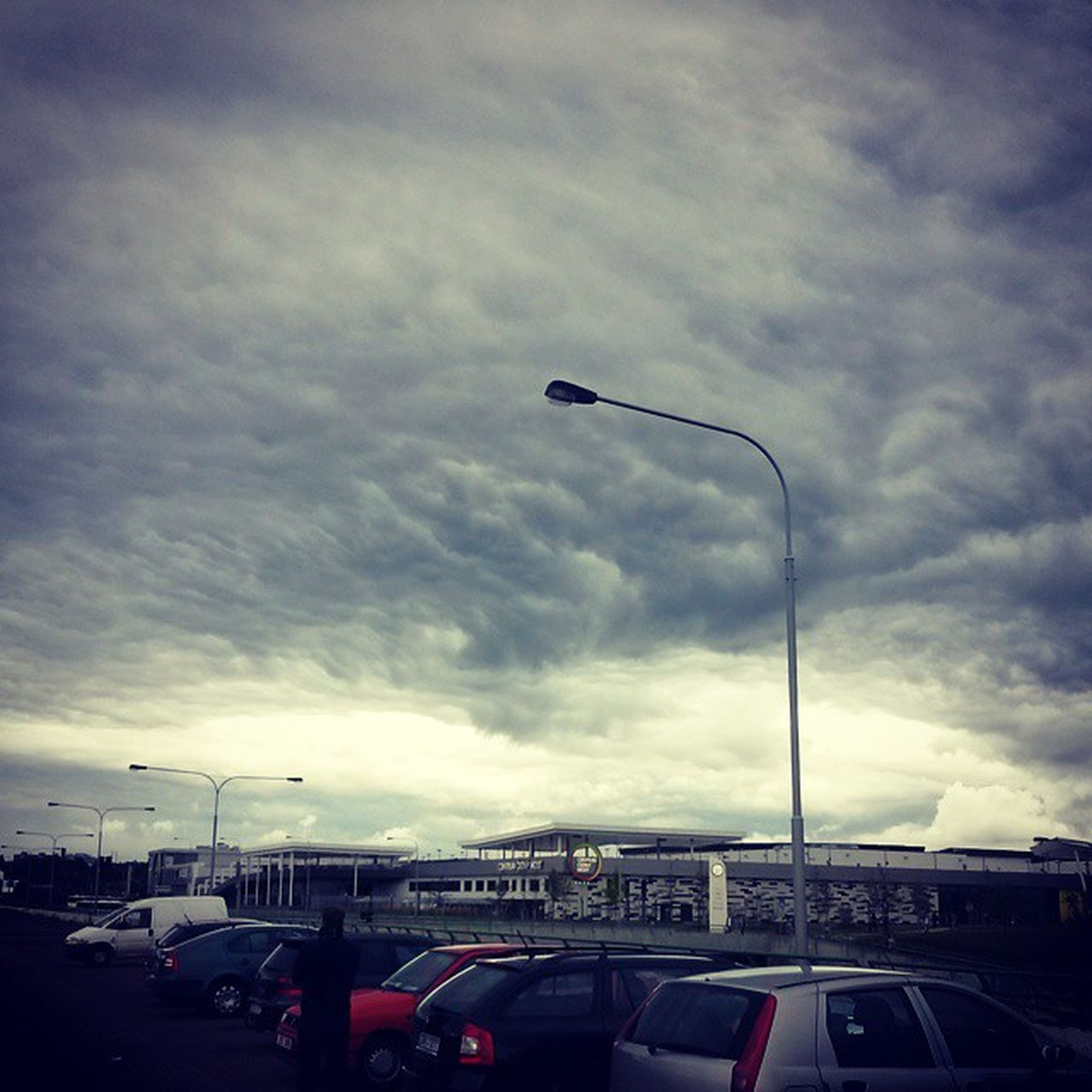 transportation, car, land vehicle, mode of transport, sky, cloud - sky, street light, road, cloudy, street, on the move, traffic, built structure, low angle view, building exterior, architecture, overcast, cloud, city, weather