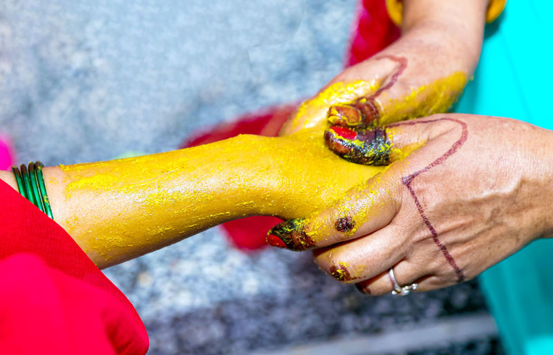 Close-up of hand holding yellow ring