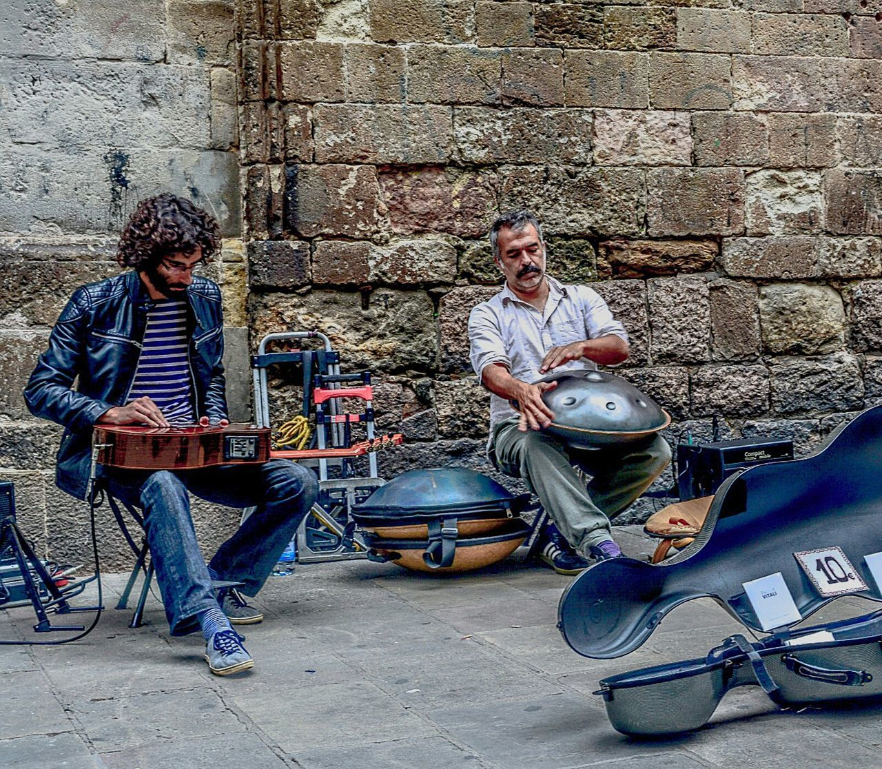 two people, music, arts culture and entertainment, leisure activity, sitting, musical instrument, togetherness, men, guitar, adult, friendship, people, plucking an instrument, playing, musician, day, full length, electric guitar, outdoors, adults only, only men