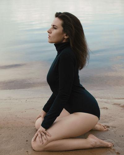 Sensuous woman sitting on beach