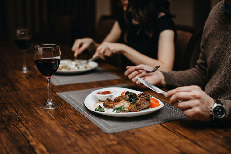 Midsection of man and woman having food in restaurant