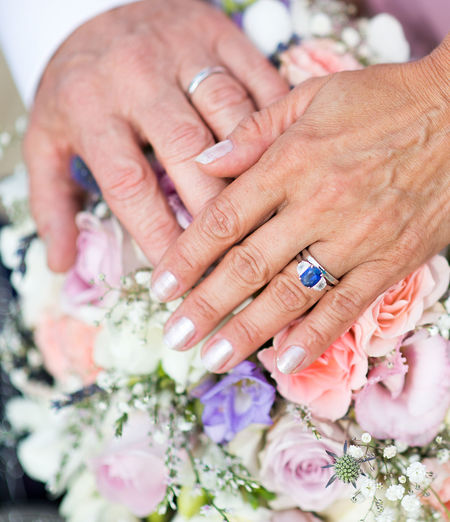 Cropped Hands Of Bride And Bridegroom Touching Bouquet