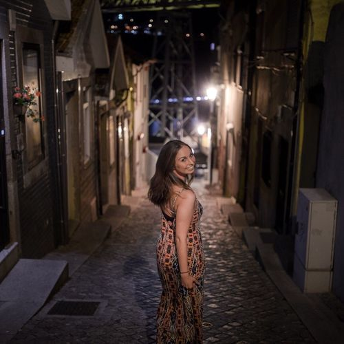 Portrait of young woman standing on footpath at night