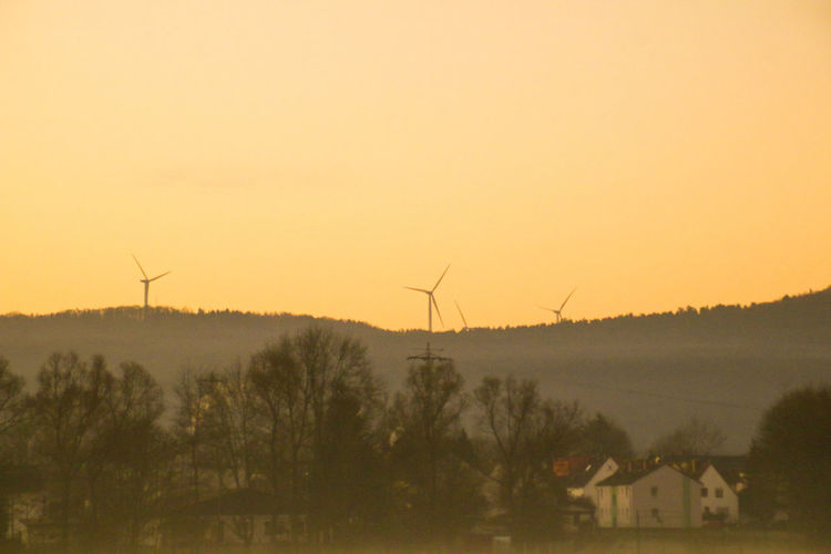 Silhouette wind turbines on field against sky during sunset