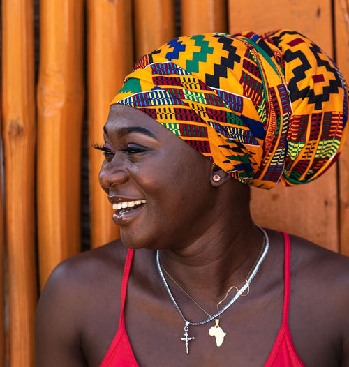Happy african woman in the small village of keta located in ghana, dressed in african headdress