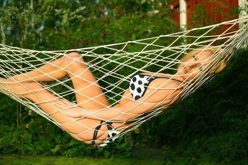 Portrait of seductive woman wearing bikini while lying in hammock