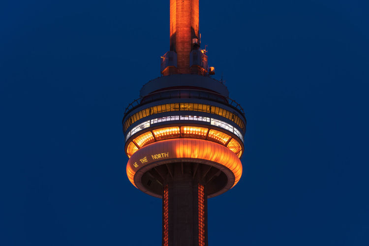 Close-up of the illuminated CN-Tower in Toronto Sky Architecture Blue Built Structure Clear Sky Tower Illuminated Tall - High Low Angle View No People Building Exterior Travel Destinations Spire  Outdoors City Night CN Tower Toronto We The North Structure Landmark Tourist Destination Canada Ontario