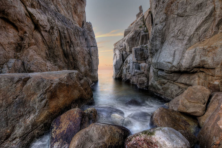 Panoramic shot of rock formation in sea against sky