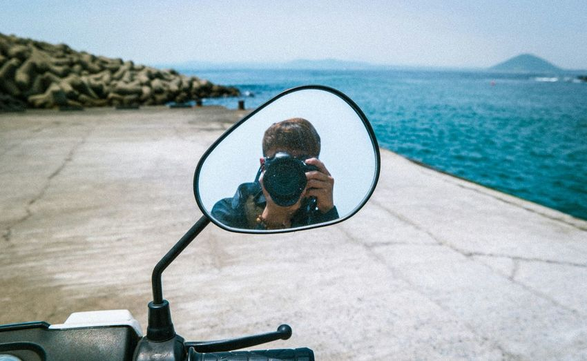 Man photographing while reflecting on side-view mirror