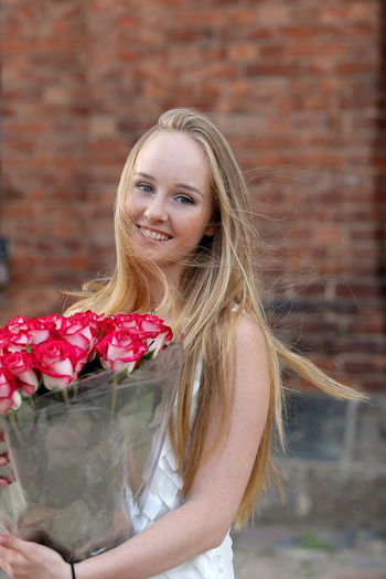 Portrait of a beautiful young woman with red flower