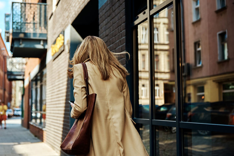 Woman in coat walks at city stret