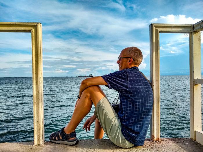 Man sitting by sea against sky