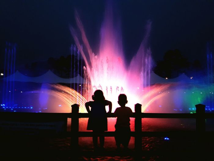 Silhouette of children by fountain at night