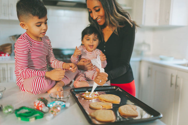 Mother preparing cookies with children at home