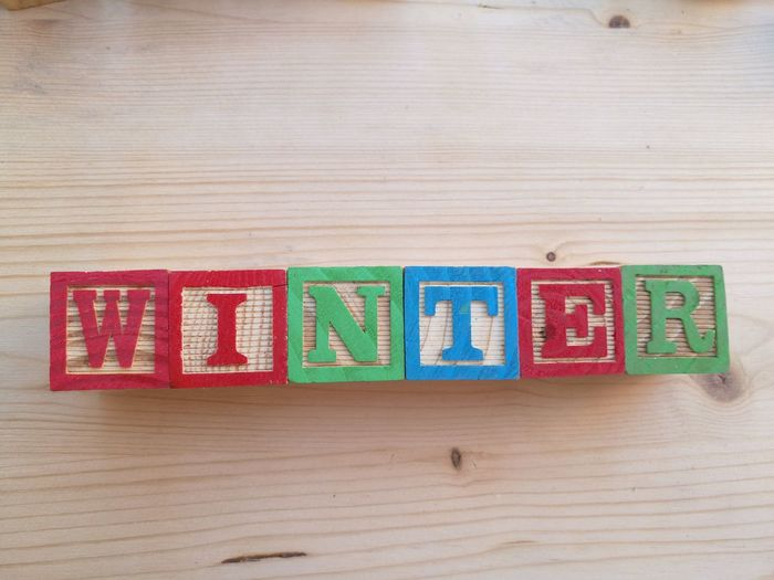 High angle view of winter text carved on wooden toy blocks