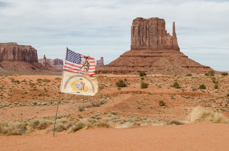 American Flag Arizona Gerónimo Monument Valley Utah Architecture Arid Climate Cloud - Sky Day Desert Flag Land Landscape Nature Navajo No People Rock Rock - Object Rock Formation Sand Sky Solid Travel Travel Destinations Wind