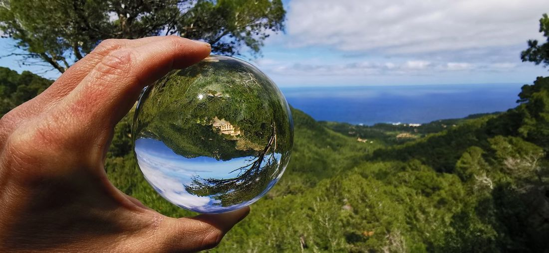 Cropped hand holding crystal ball against sky