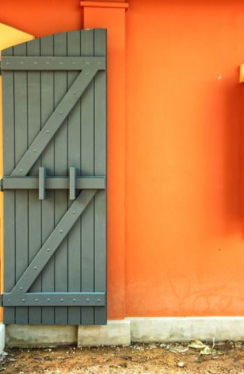 Beautiful wooden door on the orange wall. Wall - Building Feature Door Orange Color Built Structure Architecture No People Building Exterior Outdoors Day Close-up Retro Scenics Copyspace Texture Wall Art Decoration Decorative Design Decorate Wallpaper Surface Background Decor Home