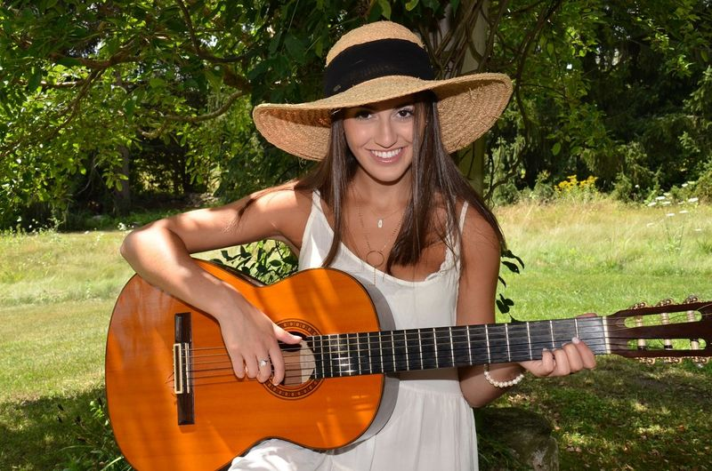 Portrait of beautiful woman playing guitar on field