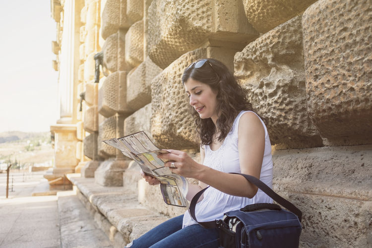 Woman using map while sitting outdoors