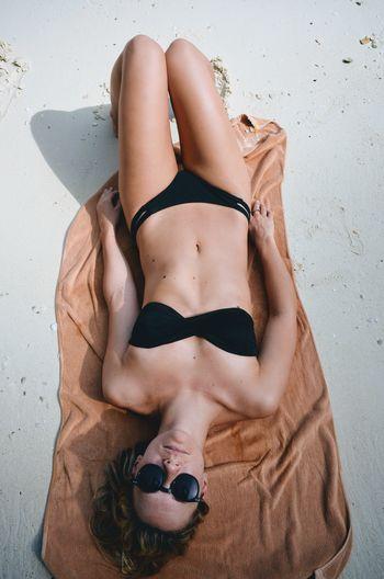 High Angle View Of Young Woman In Bikini Lying At Beach
