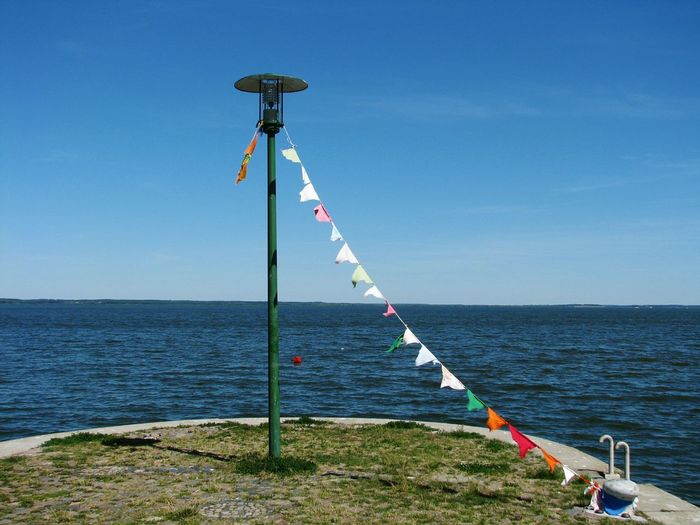 Bunting Flags Hanging Amidst Bollard And Lamp Post By Sea Against Blue Sky