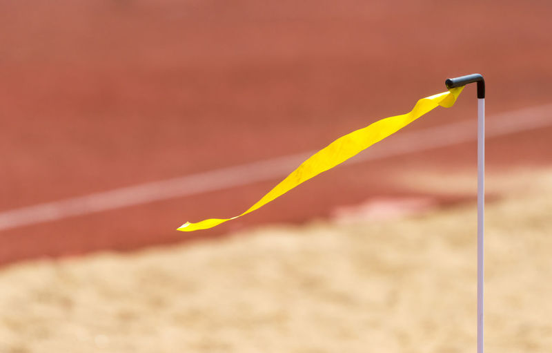 Close-up of yellow rope on sand