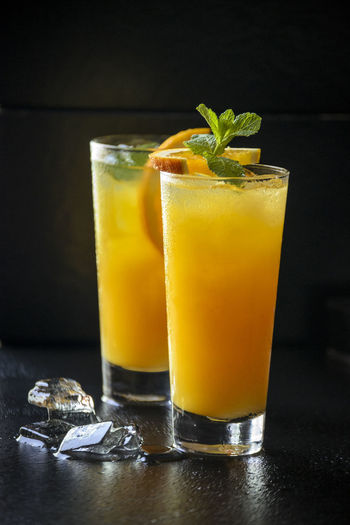Two glasses of orange drink with ice cubes on black surface
