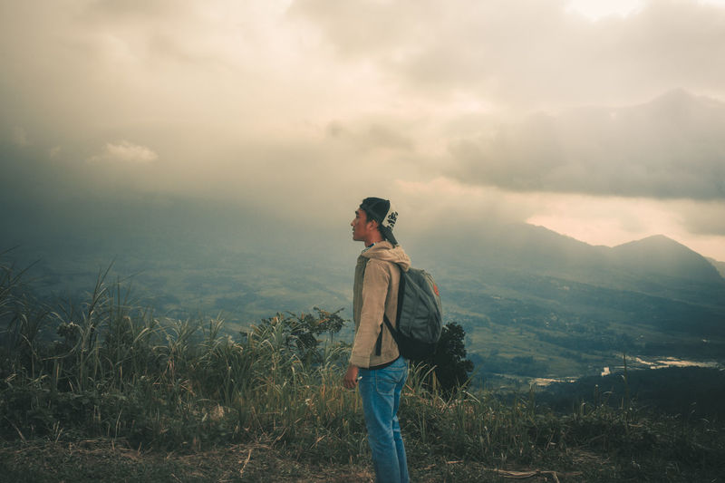 Young man standing on mountain against sky