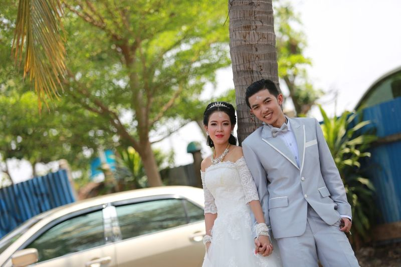 Portrait of smiling bride and groom standing against tree trunk