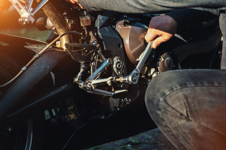 Midsection of mechanic repairing motorcycle