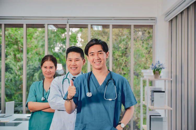 Portrait of smiling doctors gesturing while standing at hospital