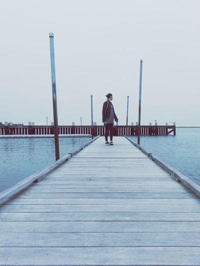 Full Length Of Woman Standing On Pier Against Sky