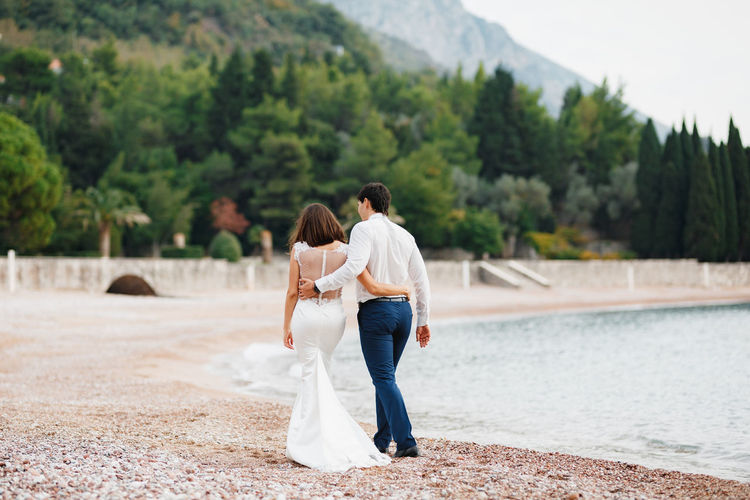 Rear view of couple standing on shore against trees