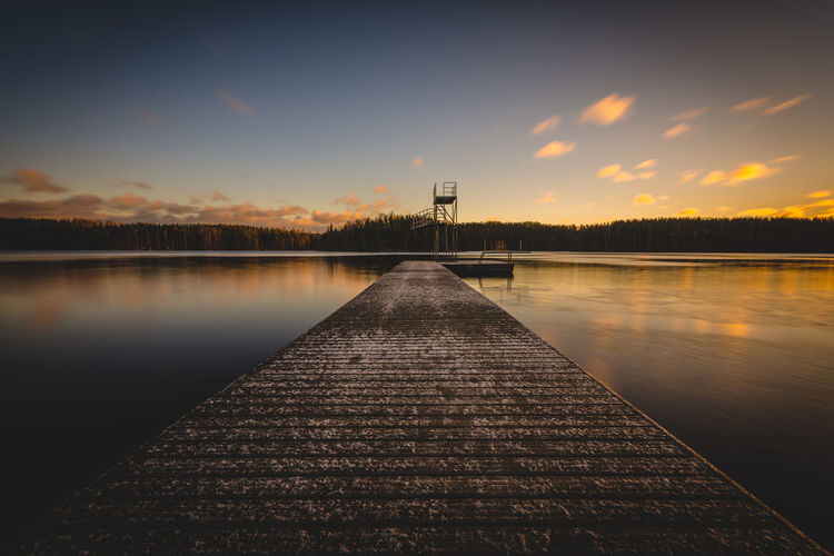 Pier Amidst Lake Against Sky During Sunset