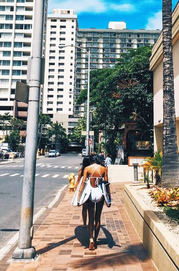 Rear View Of Woman Carrying Surfboard On Street