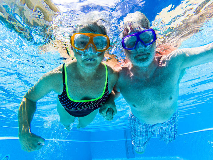 Adult people senior couple have fun swimming in the pool underwater with colored funny diving masks - dive concept and active retired man and woman enjoying the lifestyle - blue water and caucasian adults Pool Swimming Pool Water Underwater Swimming Males  Child Men Two People Swimwear Family Childhood Swimming Goggles Sea Eyewear Lifestyles Leisure Activity Trip Togetherness Females Woman Grandparents Couple Senior Adult Retirement Clear Blue Water Vacations Enjoying Life Sport Healthy Wellness Movement Activity Active Caucasian