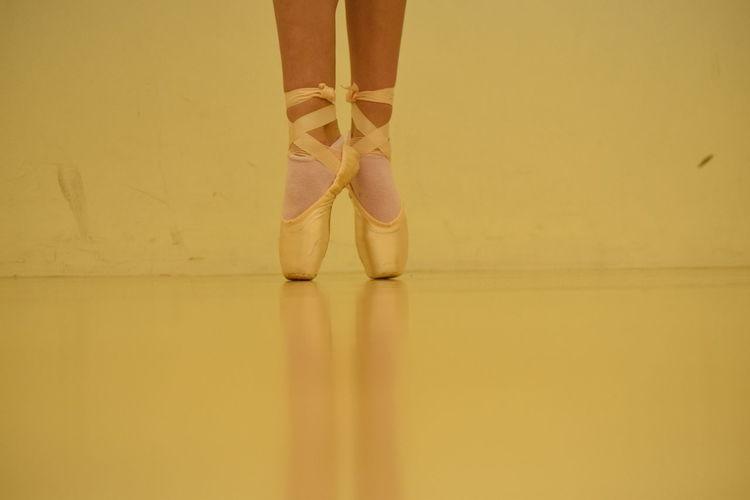 Low section of ballet dancer tiptoeing on floor
