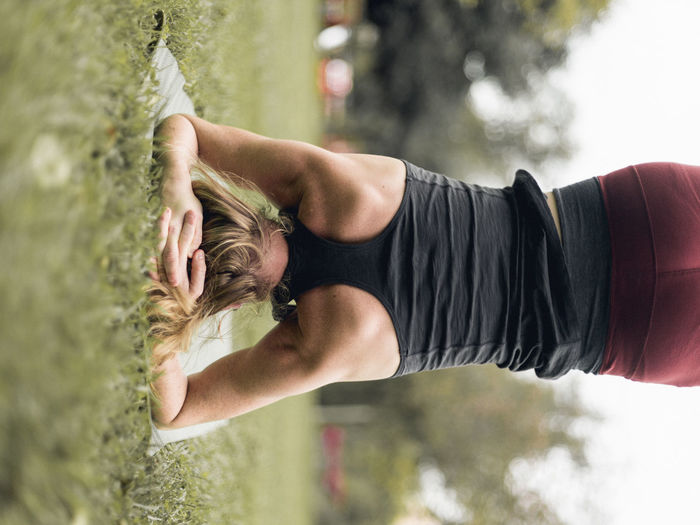 Rear view of woman practicing headstand on grassy field