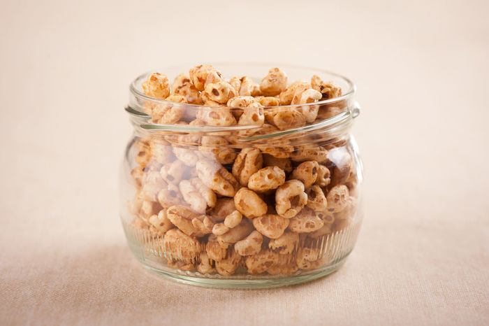 Crisp popped wheat grains in glass jar on beige material, healthy puffed cereal food staple in studio shot, horizontal orientation, nobody. Cereal Crisp Crispy Crunchy Edible  Food Glass Jar Grain Grains Healthy Eating No People Popped Prepared Puffed Roasted Seed Seeds Snack Snack Snacks Wheat