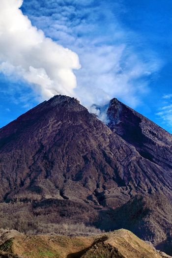 Scenic View Of Mt Merapi Steaming Against Blue Sky