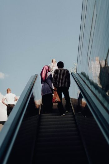 Low Angle View Of People On Escalator Against Sky