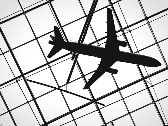 Low angle view of toy airplane hanging from glass ceiling at frankfurt airport