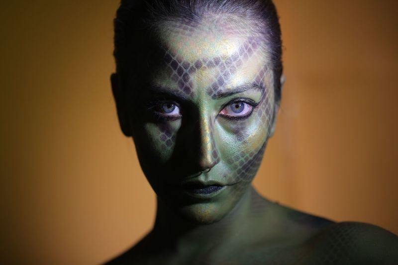 Portrait Of Young Woman With Face Paint Against Colored Background