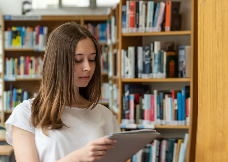 Teenage girl holding file while standing in library