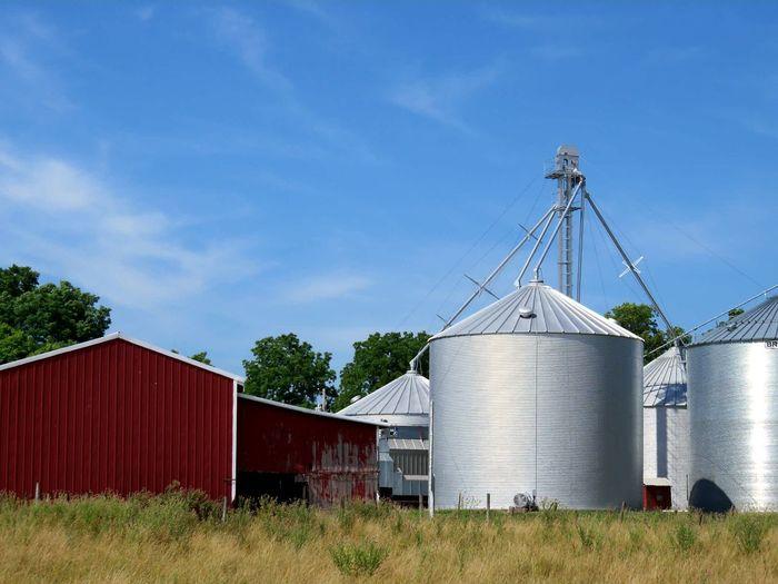 Silos and barn against sky