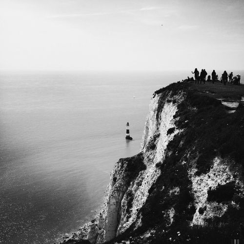 Black and white scenery with rock cliff and seaside
