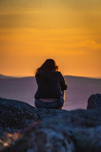 Rear view of teenage girl sitting on rock against sky during sunset