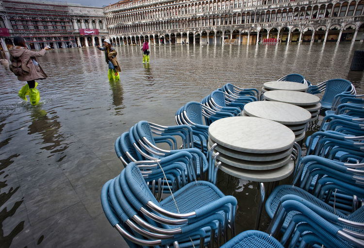 Blue stacked chairs on water filled walkway during flood at piazza san marco
